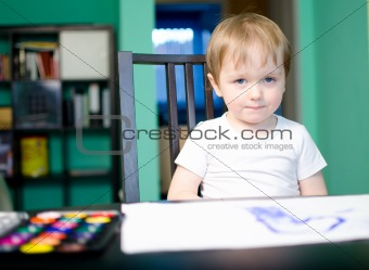 Little boy painting with watercolors