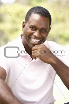 Portrait Of Young Man Sitting In Park
