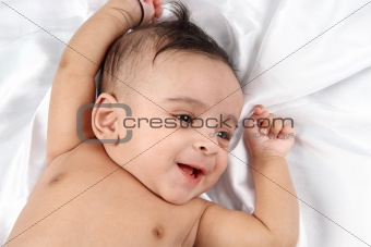 Smiling Baby on white satin background