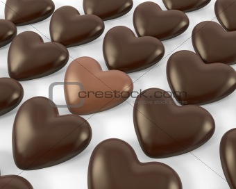 Heart shaped milk chocolate candy between dark ones