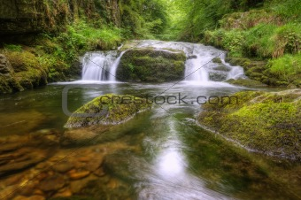 Stunning waterfall flowing over rocks through lush green forest 