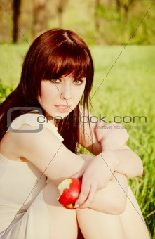 Beautiful young girl sitting on grass with apple in hand