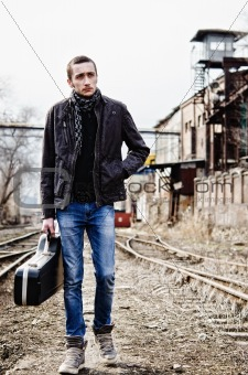 Young musician with guitar case is going among industrial ruins