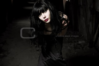 Closeup portrait of beautiful goth girl in dark tunnel