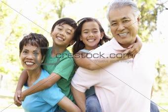 Portrait Of Grandparents With Grandchildren In Park