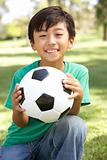 Portrait Of Young Boy In Park With Football