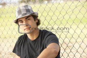 Teenage Boy Sitting In Playground Wearing Hat