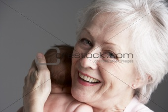 Studio Shot Of Grandmother Cuddling Granddaughter