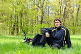 Happy man cyclist with bike and backpack sitting on green grass