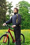 Happy man cyclist with bike among the green nature