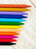 twelve color pastel crayon  close up with woody texture background