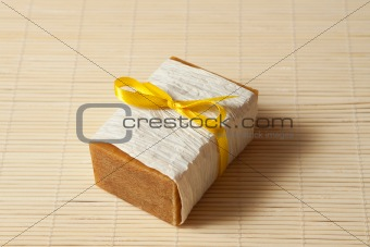 natural soap tied with a ribbon on a bamboo mat