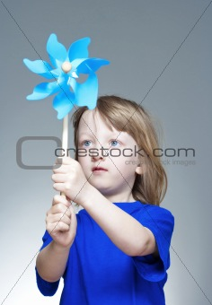 boy with long blond hair in blue top playing with a pinwheel