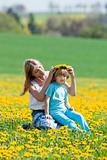 mother and son picking flowers at dandelions field in spring