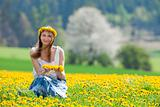 woman sitting in a dandelion field looking at camera, smiling