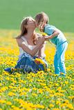mother and son kissing on dandelion field in spring