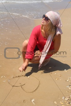 Beautiful woman at the beach drawing heart on the sand