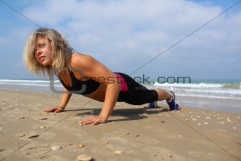Beautiful woman at the beach, doing push-ups