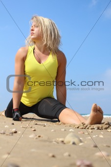 Beautiful blonde woman at the beach, doing a split