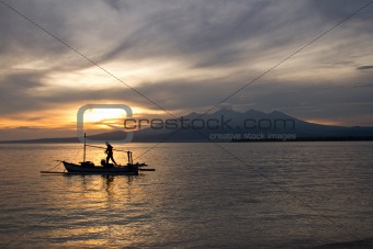 Sunrise above volcano Rinjani with fishing boat, Lombok