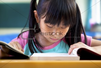 little girl studying in classroom at school