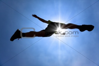 The Silhouette of runner crossing sky with sunlight background