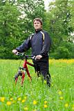 Man cyclist with bike among the green nature
