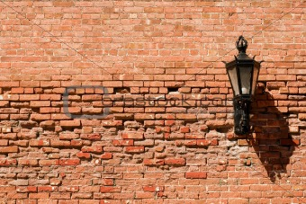 Old brick wall with lamp on it.