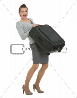 Tired traveling woman raising suitcase