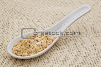 maca root powder on a ceramic spoon
