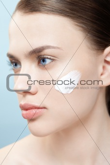 Beautiful woman apply moisturizer cosmetic cream on face