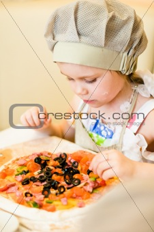 Little girl adding ingredients in pizza