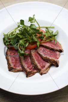 Slices of beef with tomatos and salad