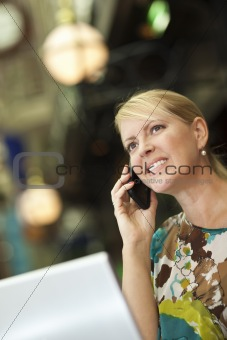 Beautiful Blonde Woman On Her Cell Phone and Laptop Computer in the City Lights.