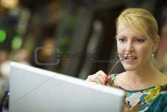Beautiful Blonde Woman Using Her Laptop Computer in the City Lights.