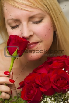 Beautiful Woman Smelling a Bunch of Red Roses.