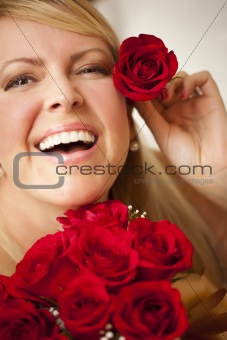 Beautiful Woman with a Bunch of Red Roses and Places One Above Her Ear.