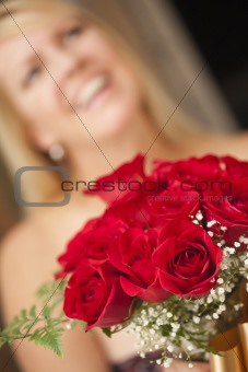 Surprised Attractive Blonde Woman Accepts Gift of Red Roses.