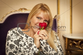 Seated Beautiful Blonde Woman Smiling While Smelling Red Rose.