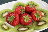 Kiwi and strawberries on a white dish