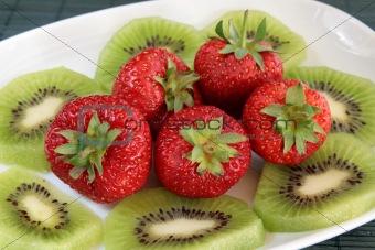 Kiwi and strawberries on a white dish