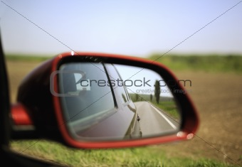 Road and trees reflected in rear-view mirror
