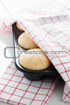 Yeast dough in a muffin pan with a white and red towel on white