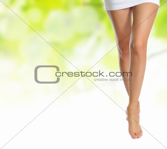 slender female legs making step over green