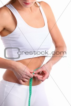 Young woman measuring her waist over white