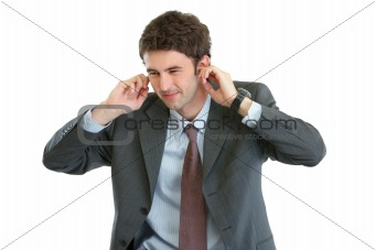 Portrait of scared businessman closing ears with fingers