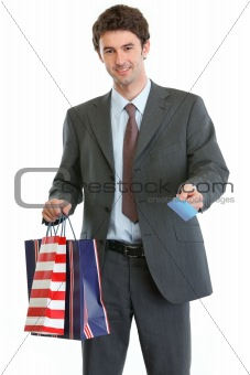 Man in suit holding shopping bags and credit card