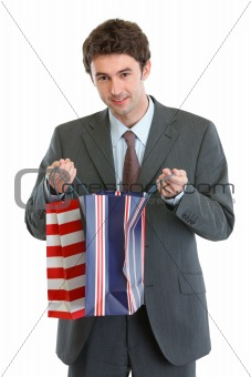 Man in suit looking into shopping bag