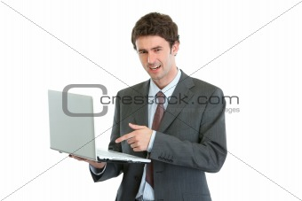 Angry businessman pointing in laptop