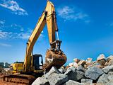 Yellow tracked excavator with rock